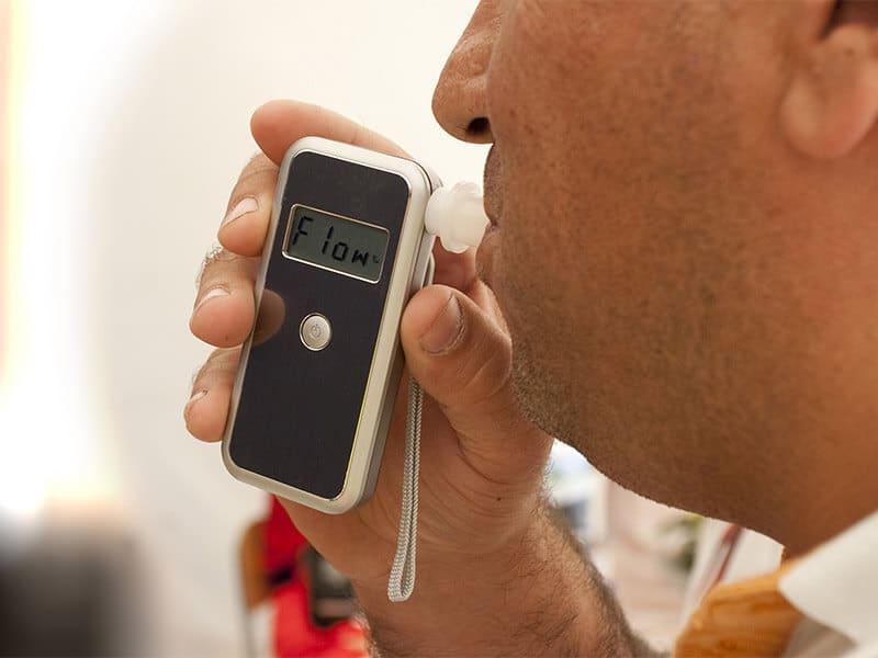 A man blows into a breath test apparatus