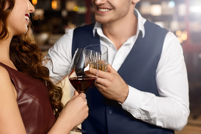 man and woman having drinks at a local bar