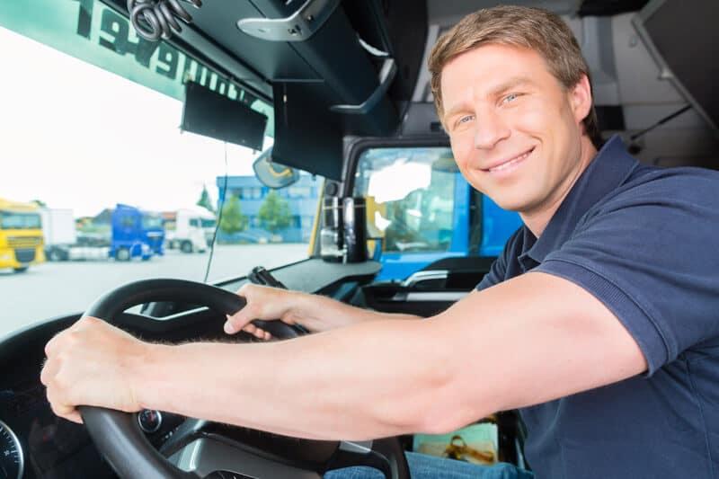 smiling man sitting inside commercial truck