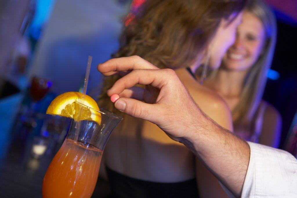 man putting date rape drug in drink