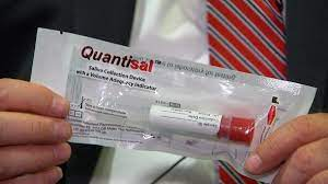 a person holding a sealed oral fluid test kit